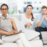 Marriage Counsellor with unhappy couple in therapists office
